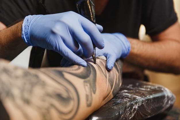 黒インクで機械によって若い男の腕に入れ墨をしているプロの刺青師アーティストのクローズアップ