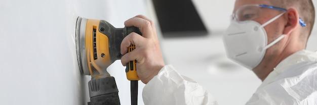 흰색 보호 얼굴 마스크를 착용하고 노란색 샌더 기계로 작업하는 전문 작업자의 근접