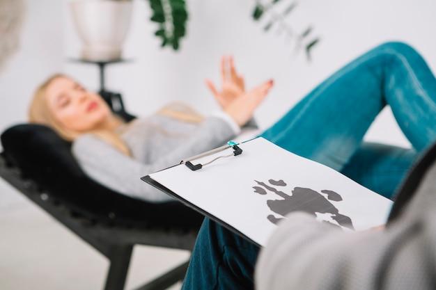 ソファに横になっている彼女の患者の心理学者診断インクブロットテストロールシャッハのクローズアップ