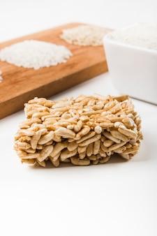 흰색 배경으로 생 쌀된 백미와 부풀어 쌀 바의 근접