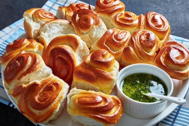 Крупным планом булочки pull apart, домашние дрожжевые обеденные булочки на белом блюде с чесночным соусом из петрушки в миске на бетонном столе, горизонтальный вид сверху