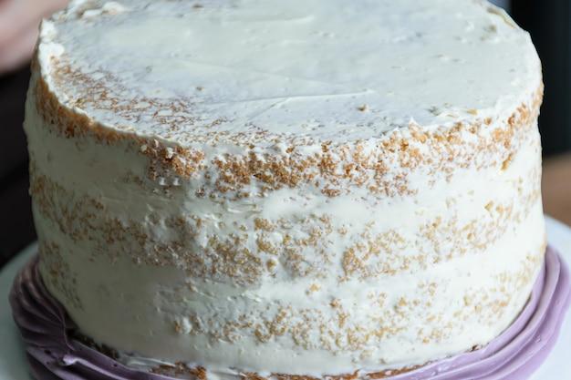 완료되는 보라색 버터 크림 케이크의 클로즈업.