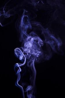 Крупный план фиолетового дыма, закрученного на черном фоне