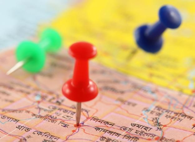 Крупным планом канцелярские кнопки, указывающие место на бумажной карте