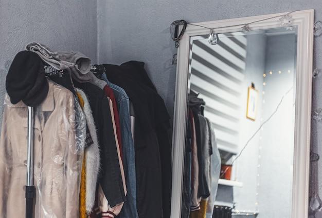 大きな白い鏡の近くのハンガーに服を着たラックのクローズアップ。