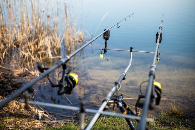 Закройте стойку с удочками на берегу озера, рыбак ждет пресноводную рыбу, рыбалку, рыбалку