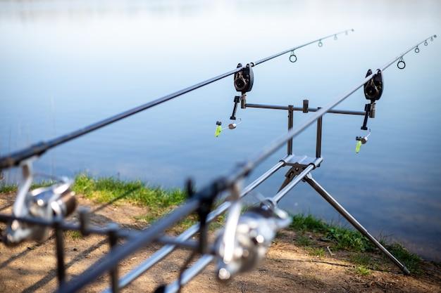 湖のそばの釣り竿、淡水魚を待っている漁師、釣り、釣りスポーツでラックのクローズアップ