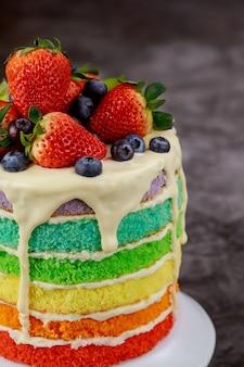 新鮮なベリーで飾られたレインボーバースデーケーキのクローズアップ。