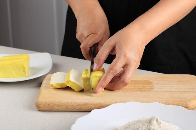 나무 보드에 칼로 큐브로 절단 원시 콩 노란색 반둥 두부의 클로즈업