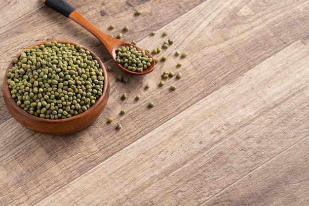 木製のテーブルの背景にボウルに生緑豆のクローズアップ。