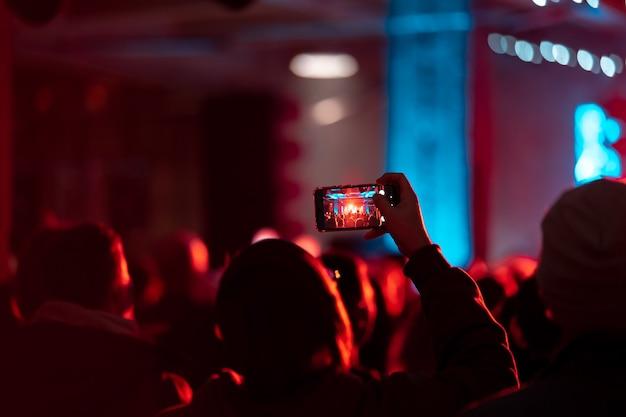 Крупным планом записи видео с помощью смартфона во время концерта. тонированное изображение