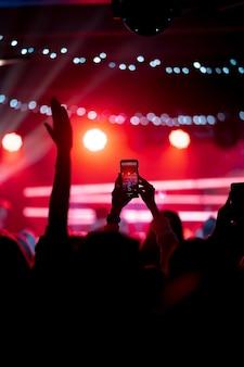 コンサート中にスマートフォンでビデオを録画するクローズアップ。トーンの写真