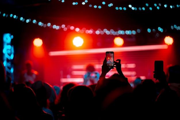 コンサート中にスマートフォンでビデオを録画するクローズアップ