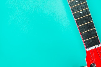 Close-up of red acoustic classic guitar on turquoise backdrop