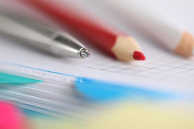 赤と白の鉛筆のクローズアップ。テーブルの上の銀のペン。独創的なアイデアとメモのためのノート。事業会社。時間管理と事務用品のコンセプト
