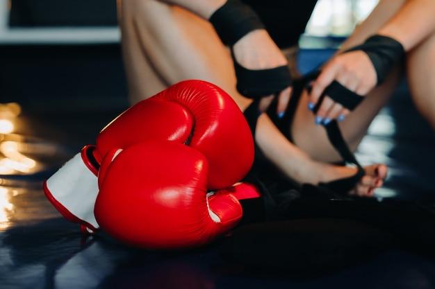 青いボクシングのリングの床にある赤いボクシンググローブのクローズアップ。