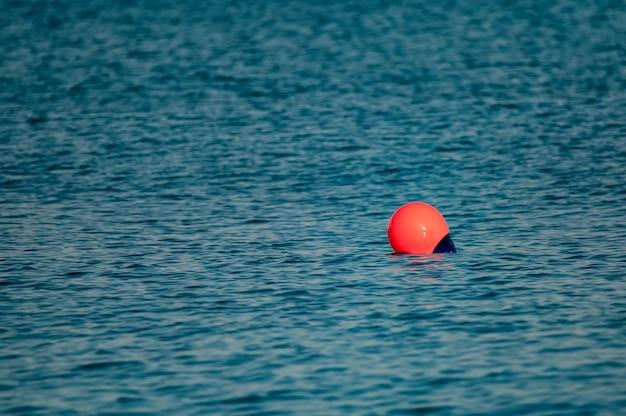 海の波の間に浮かぶ赤いブイのクローズアップ