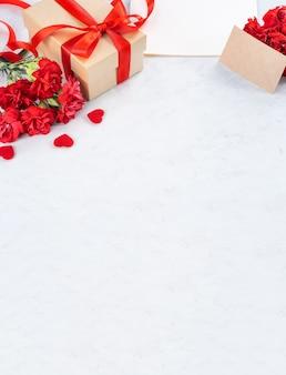 어머니의 날 인사말을위한 선물 상자가있는 빨간 카네이션의 닫습니다