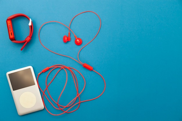 青い紙の背景にスポーツ時計と音楽プレーヤーと赤いイヤホンのクローズアップ。