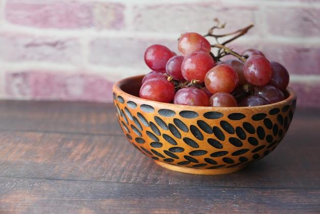 テーブルの上のボウルに赤ブドウのクローズアップ