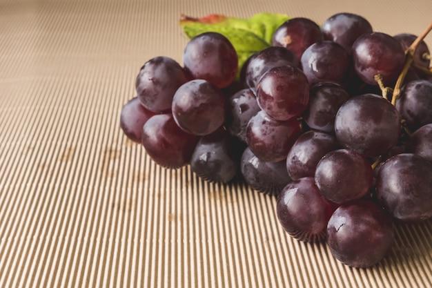 Закройте красный виноград на деревянном столе