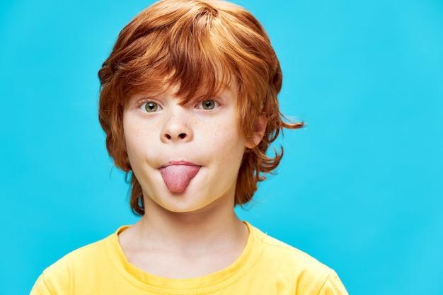 빨간 머리 소년 혀를 튀어 나와 노란색 티셔츠 파란색 격리 된 배경의 근접