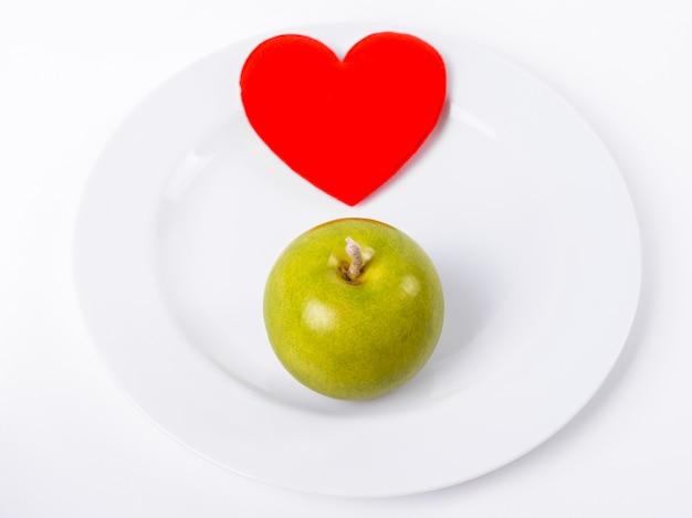 白いプレート上の緑のリンゴと赤いハートのクローズアップ