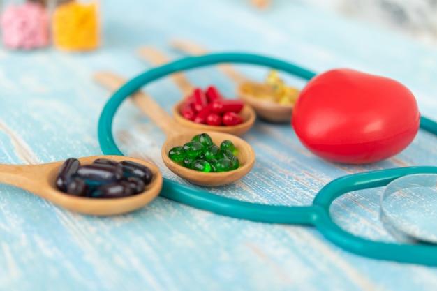 Крупным планом красные сердца и витамины.