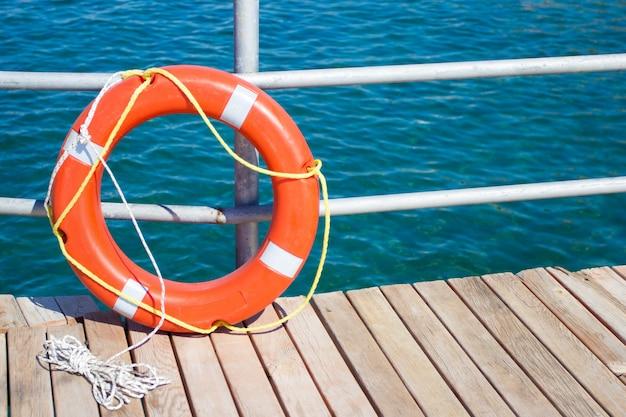 Крупным планом красный спасательный круг на деревянном пирсе на пляже