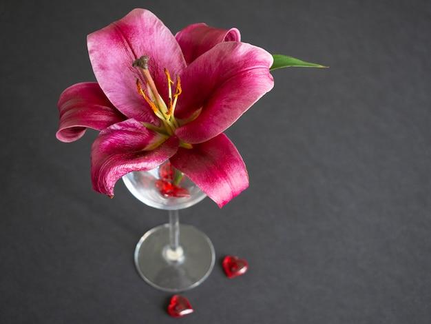 黒のガラス花瓶の赤いユリの花のクローズアップ。