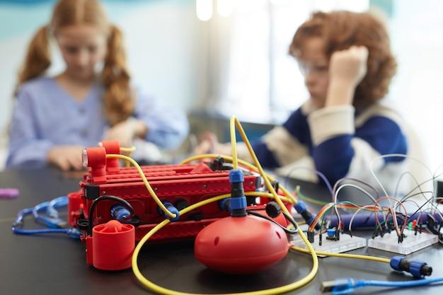 Крупным планом красная роботизированная машина на столе в инженерном классе с детьми в фоновом режиме, копией пространства