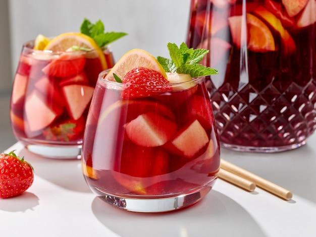 白いキッチンテーブルの上の赤いサングリアグラスのクローズアップ