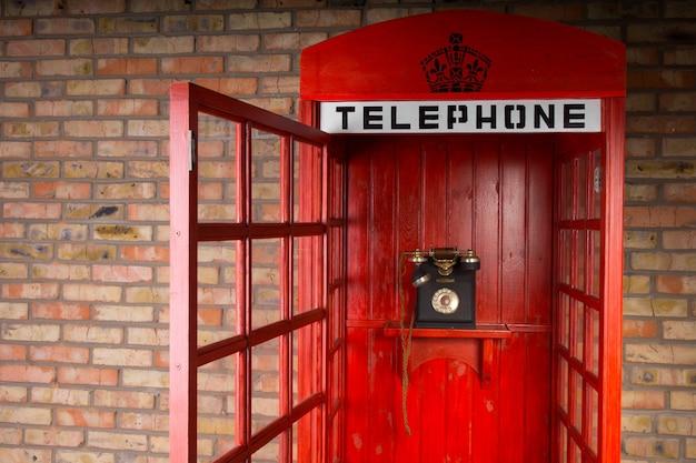 구식 전화와 열린 문을 가진 빨간 전화 부스의 클로즈업