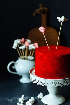 Крупный план красного бархатного торта на белой красивой подставке с зефиром на сером столе.