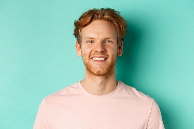 ピンクのtシャツを着た赤毛のひげを生やした男のクローズアップ、白い完璧な歯で笑って、カメラを見て、ターコイズブルーの背景の上に立っています。