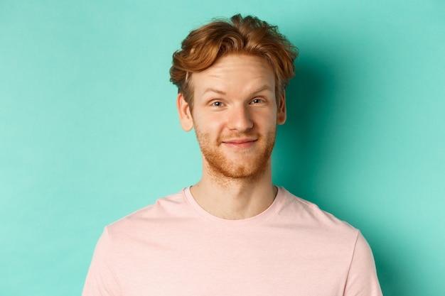 赤毛のひげを生やした男のクローズアップは、ターコイズブルーの背景にピンクのtシャツで立って、承認と笑顔でうなずきます。