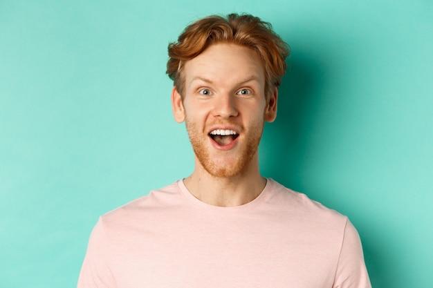 赤毛のひげを生やした男性が眉を上げ、カメラに驚いて見て、プロモーションをチェックし、ミントの背景の上に立っているのクローズアップ。