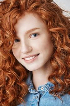 Закройте рыжий красивая девушка с веснушками улыбается.