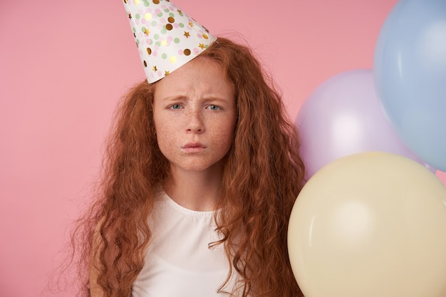 ピンクのスタジオの背景の上にお祝いの服を着て、すぼめた唇と眉をひそめている顔でカメラを見ている長い巻き毛の赤毛の女の子のクローズアップ。子供とお祝いのコンセプト
