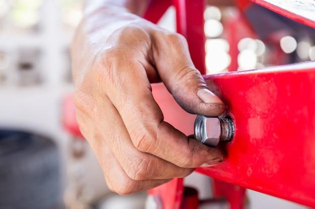수리공 손이 배관의 볼트와 너트를 설치하고 작업자의 손이 볼트의 너트를 조입니다