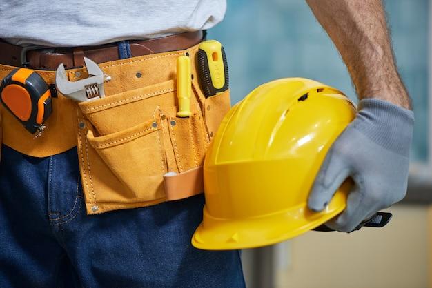 Крупный план ремонтника с поясом для инструментов с различными инструментами, держащего шлем в руке