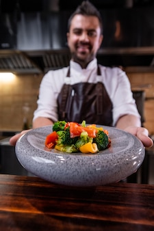 カウンターの上の丸いプレートにサラダ料理を与えるレストランのシェフのクローズアップ
