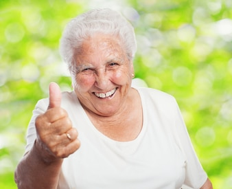 Close-up of retired woman with thumb up