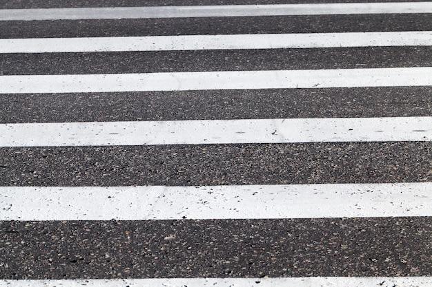 도로 표시의 클로즈업은 횡단 보도의 흰색 선인 도로에 있습니다.