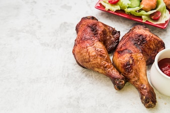 Close-up of roasted chicken leg with sauce and salad on concrete background