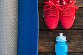 Close-up of rolled up exercise mat; sock and pair of red sport shoes on wooden table