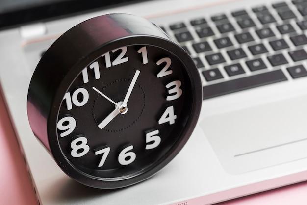 노트북에 라운드 블랙 시계의 클로즈업
