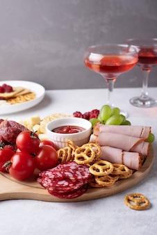 さまざまなスナックと灰色の背景に赤い酒とグラス2杯の丸い豚肉ボードのクローズアップ。