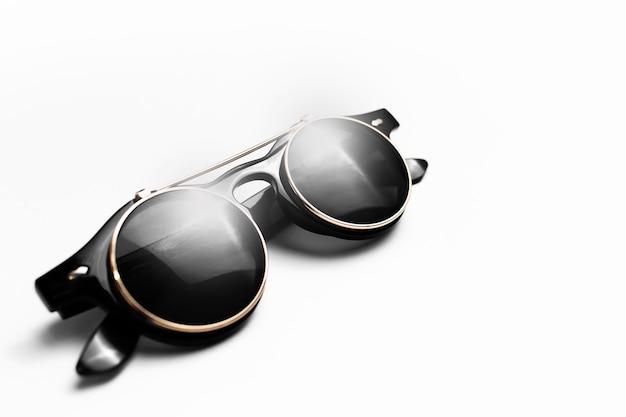 白い表面の丸いサングラスのクローズアップ。