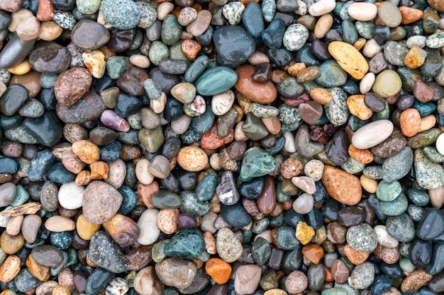 Закройте закругленные и полированные скалы пляжа.